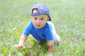 Baby age of 10 months creeps on grass — Stock Photo