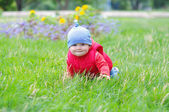 Baby in red waistcoat creeps on grass — Stock Photo