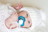 Portrait of lovely newborn with dummy in white knitted hat — Stock Photo