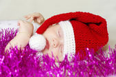 Lovely sleeping baby in New Year's hat among spangle — Stock Photo