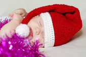 Sleeping baby in New Year's hat among spangle — Stock Photo