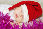 Lovely baby in New Year's hat sleeps among spangle — Stock Photo