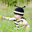 Stock Photo: Baby in bee costume reaches for flower