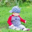 Baby age of 10 months plays sitting on grass in park — Stock Photo #34891821