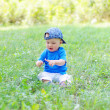 Baby sitting on grass in park with small flower in hand — Stock Photo #34892001