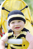 Happy baby in bee costume on baby carriage — Stock Photo