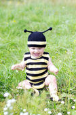 Baby age of 10 months in bee costume outdoors — Stock Photo