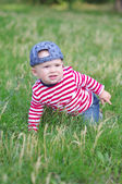 Baby creeps on grass in summer — Stock Photo