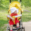 Thoughtful baby on baby carriage — Stock Photo