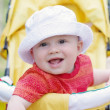Smiling baby age of 9 months on baby carriage — Stock Photo