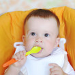 Lovely baby age of 9 months with spoon — Stock Photo