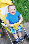 Happy baby boy on yellow baby buggy — Stock Photo