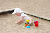 Baby age of 9 months plays with sand on playground — Stock Photo