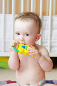 Lovely baby age of 9 months gnaws rattle — Stock Photo