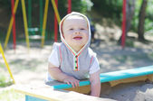Happy baby age of 9 months plays in sandpit — Stock Photo