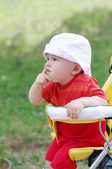Thoughtful baby age of 9 months on baby buggy — Stock Photo