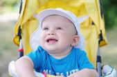 Happy baby on yellow buggy looks away — Zdjęcie stockowe