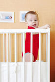 Baby standing in white bed — Stock Photo