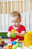 Baby plays rattle against white bed — Stock Photo