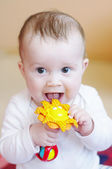 Smiling baby plays rattle — Stock Photo