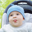 Stock Photo: Baby puts out tongue