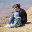 Mother and son sit on riverside — Stock Photo #35304893