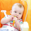 Baby sits on chair and holds spoon — Stock Photo