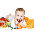 Stock Photo: Six-months baby with fabrics, ribbons and scissor