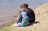 Mother and son sit on the riverside — Stock Photo