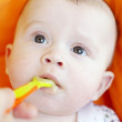 Stock Photo: Five-months baby is fed by puree from spoon