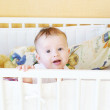 Stock Photo: Whimsical five-months baby in white bed