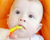 Five-months baby is fed by puree from spoon — Stock Photo