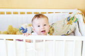Whimsical five-months baby in white bed — Stock Photo