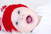 Laughing baby in red knitted hat — Stock Photo