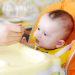 Stock Photo: Five-months baby is fed by puree