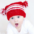 Portrait of yawning baby in red knitted hat — Stock Photo #35325231