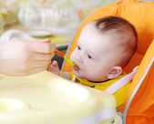 Five-months baby is fed by puree — Stock Photo