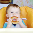Baby eats round cracknel — Stock Photo #35397975