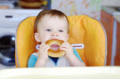 Baby eats round cracknel — Stock Photo