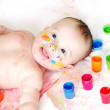 Happy baby lying among finger-type paints — Stock Photo
