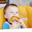 Happy baby eating round cracknel — Stock fotografie