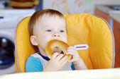 Happy baby eating round cracknel — Stock Photo