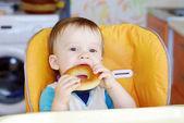 Baby boy biting round cracknel — Stock Photo