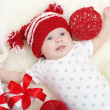 Lovely baby in red hat lying among gifts — Stock Photo #35769873