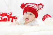 Lovely baby in red hat with gifts — Stock Photo