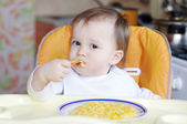 Lovely baby eats rice-milk with pumpkin — Stock Photo