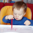 Lovely baby paints with red pen — Stock Photo