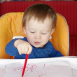 Baby paints with red pen — Stock Photo
