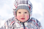 Baby with rosy cheeks in winter outdoors — Stock Photo