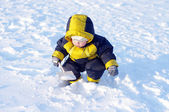 Warm dressed baby with shovel in winter — Stock Photo